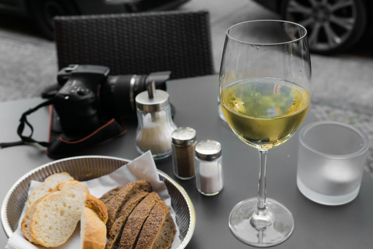 Wine with bread and camera on table