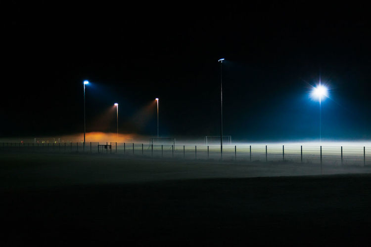 Night Illuminated Lighting Equipment Floodlight No People Street Light Sport Street Stadium Sky Absence Nature Outdoors Team Sport Copy Space Transportation Soccer Dark City Light - Natural Phenomenon Floodlit Football Mist Fog Spotlight