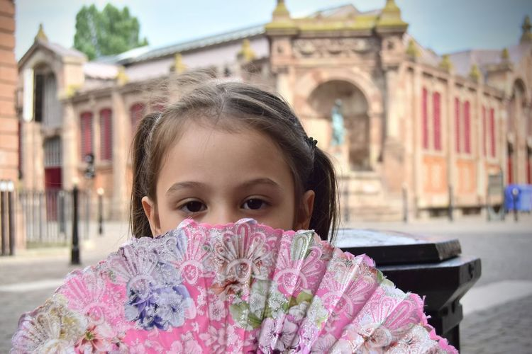 Close-up portrait of girl holding hand fan in city