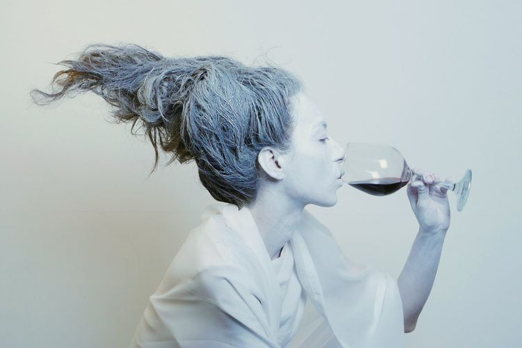 Close-up of woman drinking wine against white background