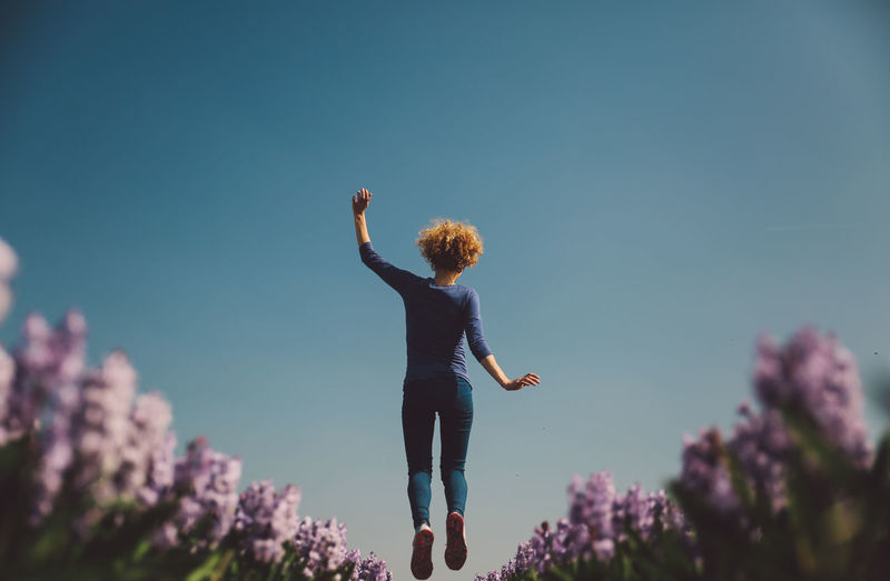 Beauty In Nature Blue Cheerful Child Clear Sky Curly Hair Day Field Flowers Girl Happiness Human Body Part Hyacinth Jumping Low Angle View Mid-air Nature Netherlands One Person Outdoors People Sky Spring Done That. Go Higher