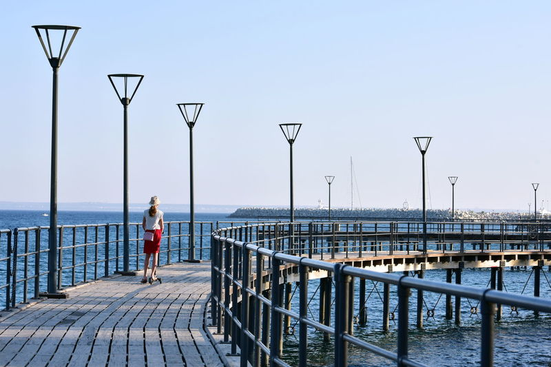 Rear view of woman standing on pier at sea against clear sky