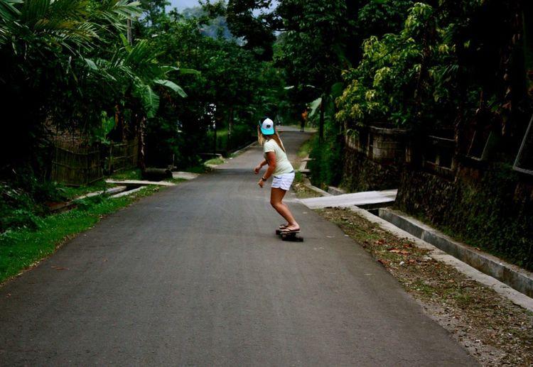 Full length of woman skateboarding on road