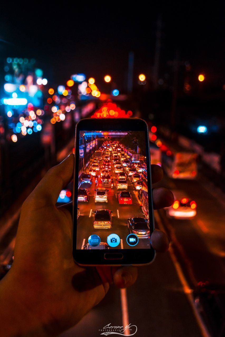wireless technology, smart phone, technology, human hand, photography themes, portable information device, illuminated, communication, hand, mobile phone, photographing, city, holding, real people, night, connection, one person, activity, human body part, architecture, finger, outdoors