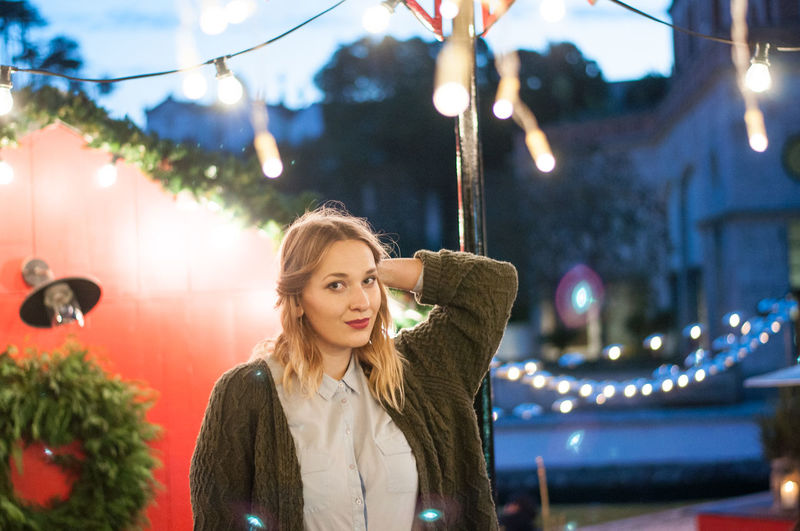 Portrait Of Young Woman Standing Against House With Christmas Decoration At Dusk