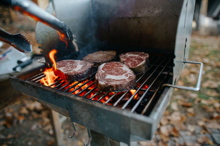 Cropped image of man preparing food on barbecue grill in yard