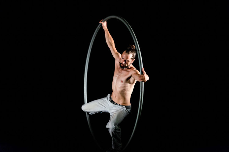 Circus Adult Agility Arms Raised Balance Black Background Dancing Effort Exercising Flexibility Full Length Healthy Lifestyle Indoors  Lifestyles Motion One Person Performance Shirtless Skill  Strength Studio Shot Vitality Young Adult