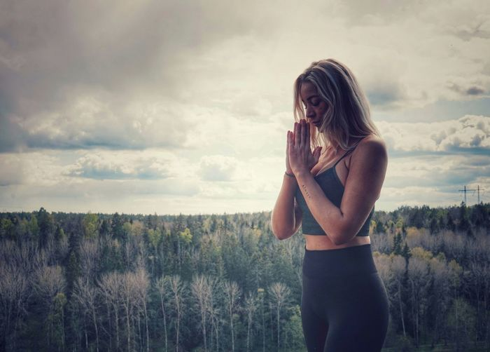 Full length of beautiful woman standing on land against sky