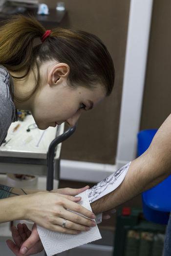 Female tattoo artist tattooing in studio