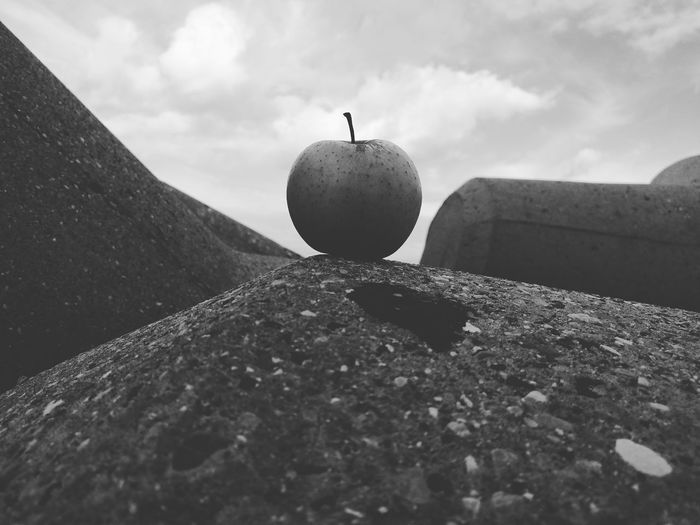 Low angle view of an apple on rock against sky