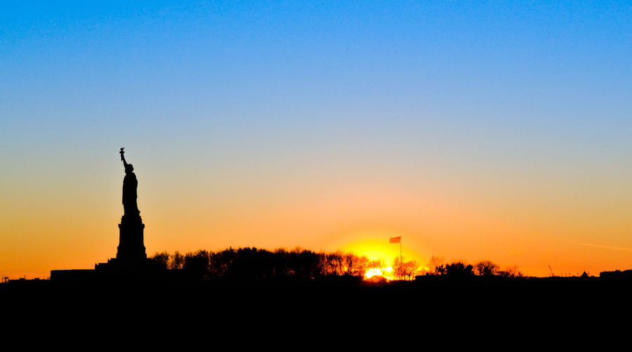 Silhouette sculpture against sky during sunset