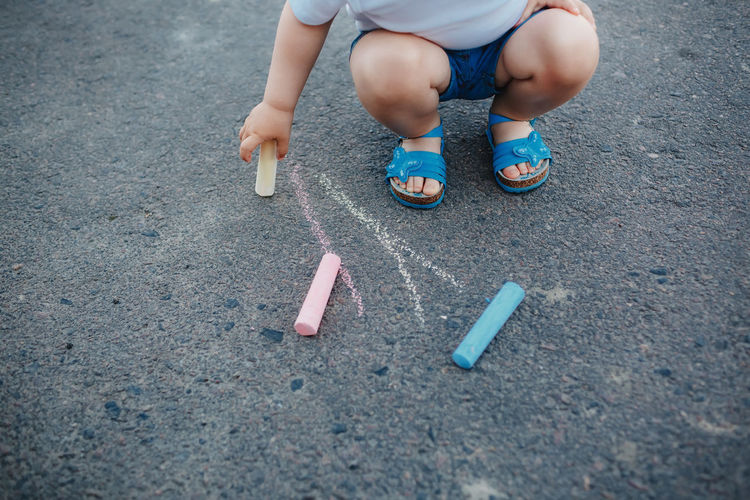 Low section of boy doodling on road with chalk