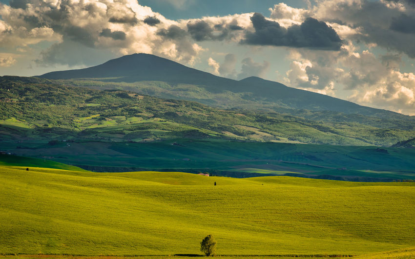 Scenic view of field and mountains against sky
