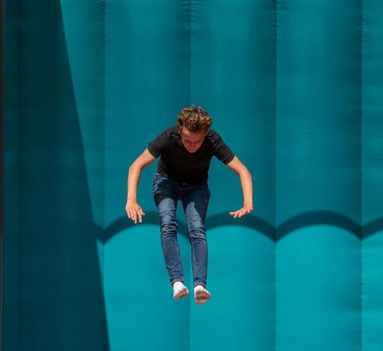 Full length of man jumping in swimming pool