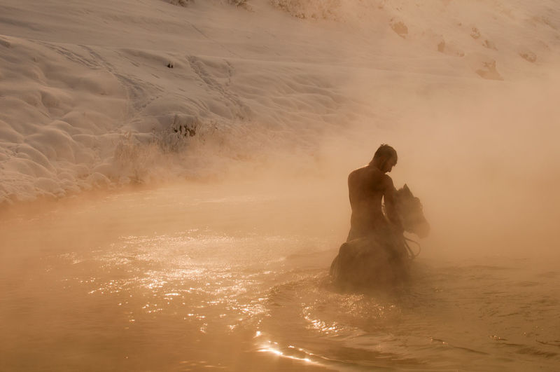 Man riding horse in muddy water during sunset