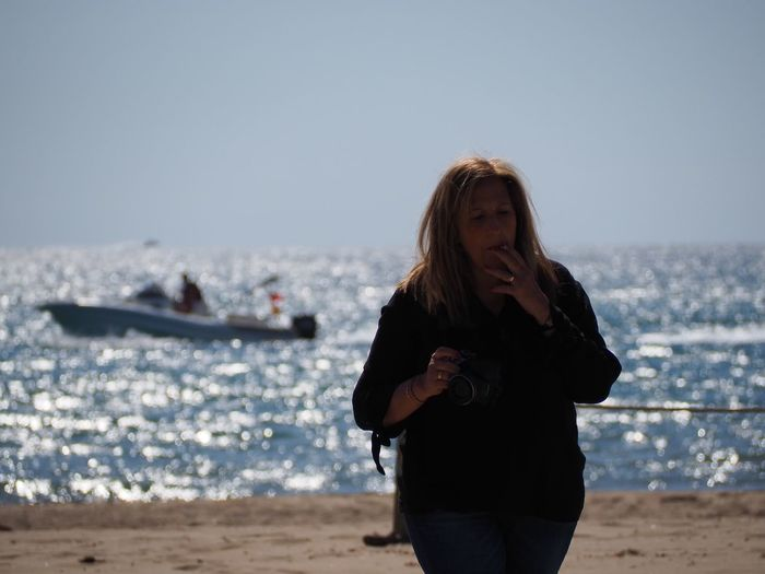 Mature Woman Smoking Cigarette While Standing Against Sea At Beach