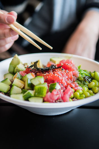Woman eating Poke / Poké Salad bowl (fish salad) Pokē Bowl Bowl Chopsticks Close-up Day Fish Salad Food Food And Drink Freshness Healthy Eating Human Hand Indoors  Lifestyles One Person Poke Ready-to-eat Real People