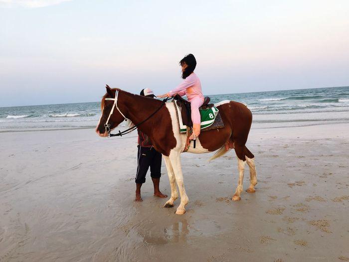 Girl riding horse at beach against clear sky