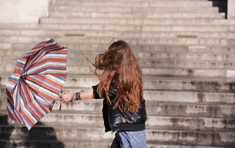Woman with umbrella walking against steps