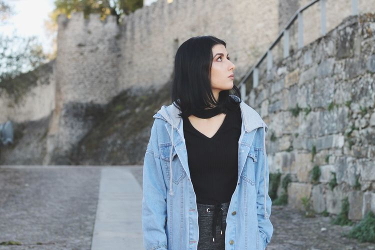 Young woman looking away against wall