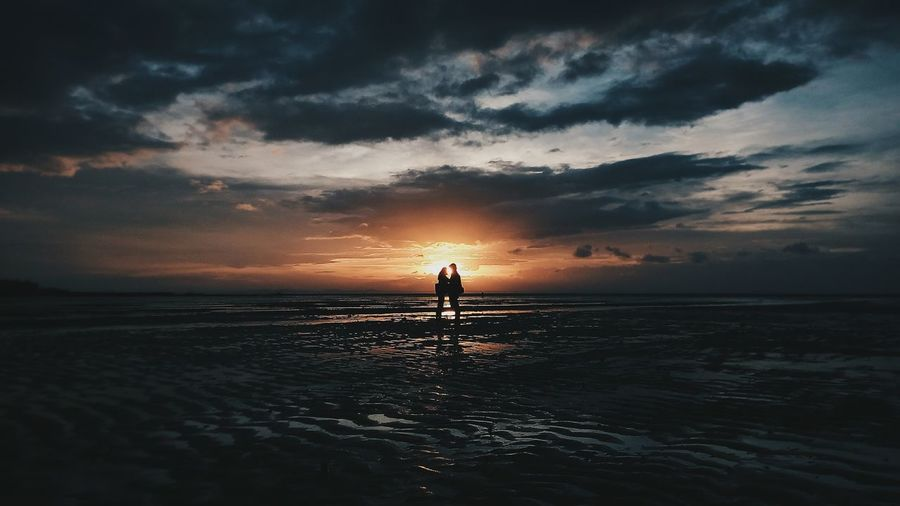 Silhouette couple standing on beach against sky during sunset