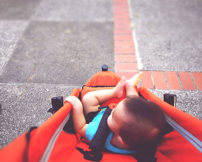 High Angle View Of Toddler In Baby Carriage On Footpath
