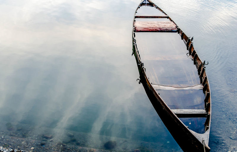 A sunken boat Water Nautical Vessel Waterfront Day Reflection Transportation Mode Of Transportation Beauty In Nature Tranquil Scene Rowboat Cloud - Sky Travel Sunken Boat Nainital India Nainital Lake
