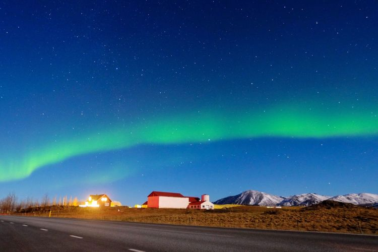 Northern lights above houses and mountain view.