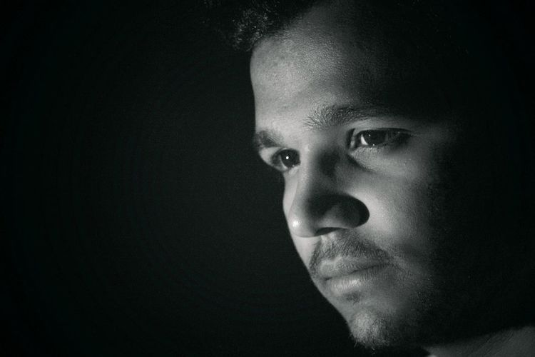 Close-up of thoughtful young man against black background