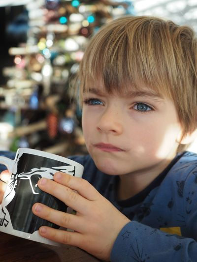 Close-Up Of Thoughtful Boy Holding Cup