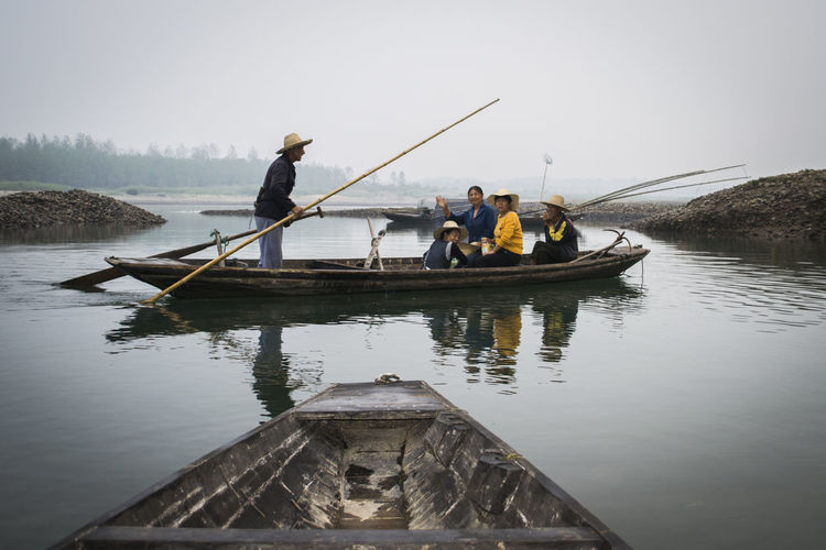 Men standing on boat in river against sky