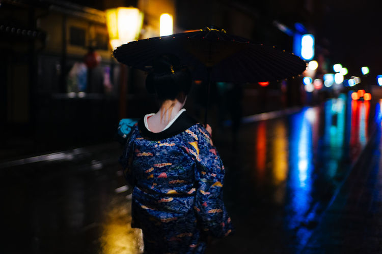 Rear view of woman with umbrella standing on street during rainy season