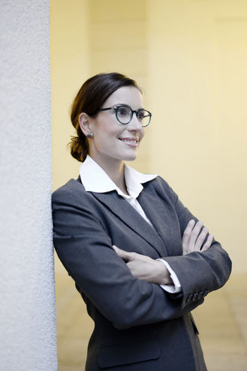 happy businesswoman leaning on wall Arms Crossed Beautiful Broker Business Business Attire Business Person Businesswear Businesswoman Confident  Contentment Glasses Happy Laughing Leaning Livestyle Manager One Person Optimistic Smiling Standing Successful Wall Woman