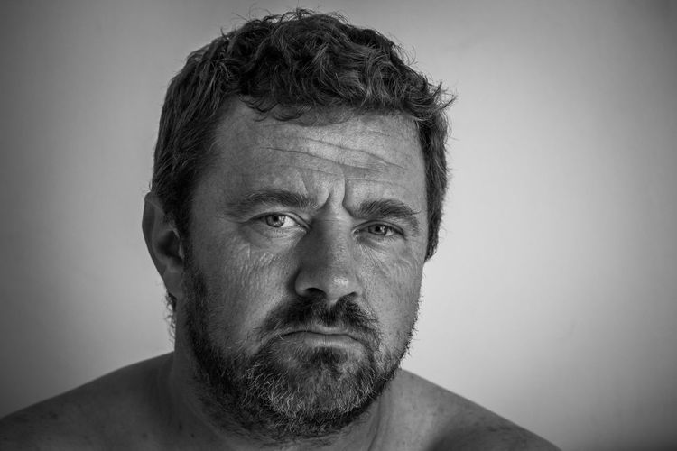 Close-up portrait of man against white background