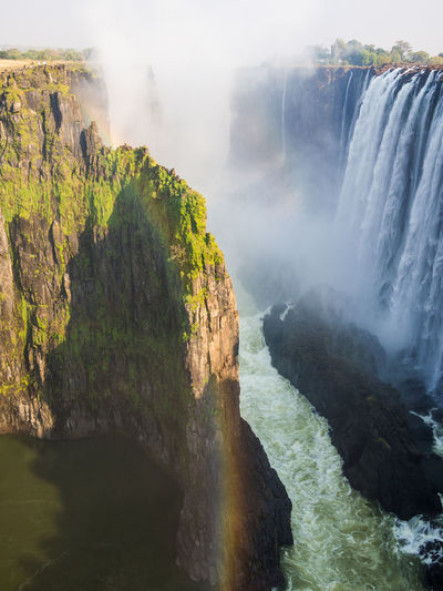 Scenic view of victoria falls waterfall with rainbow at border between zambia and zimbabwe