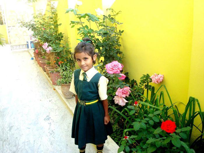 Portrait Of Girl In School Uniform Standing By Flowers At Yard