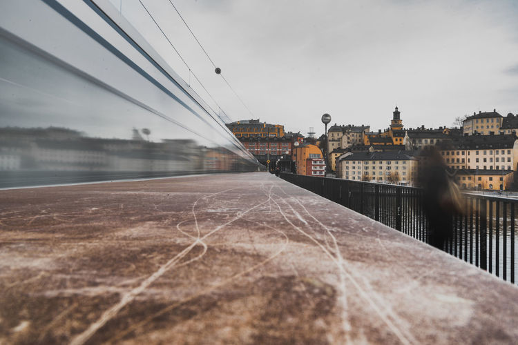 Photography In Motion. On the left a train speeds past and on the right a woman walks in the opposite direction. Architecture Blurred Motion Building Exterior Built Structure Diminishing Perspective Motion Motion Blur Movement Moving Train Photography In Motion Photography ın Motion Sky Stockholm Train Transportation