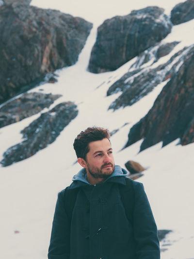 Man Looking Away Against Snowy Rocks