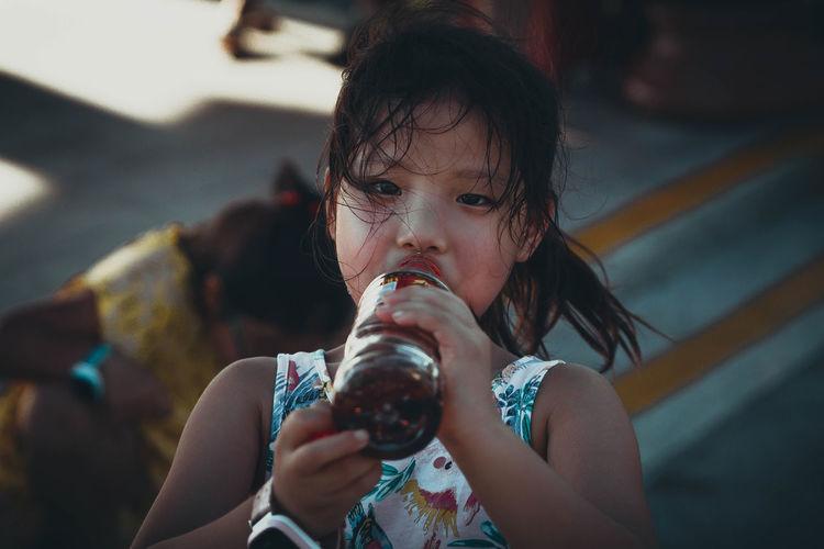 Full length portrait of a girl drinking glass