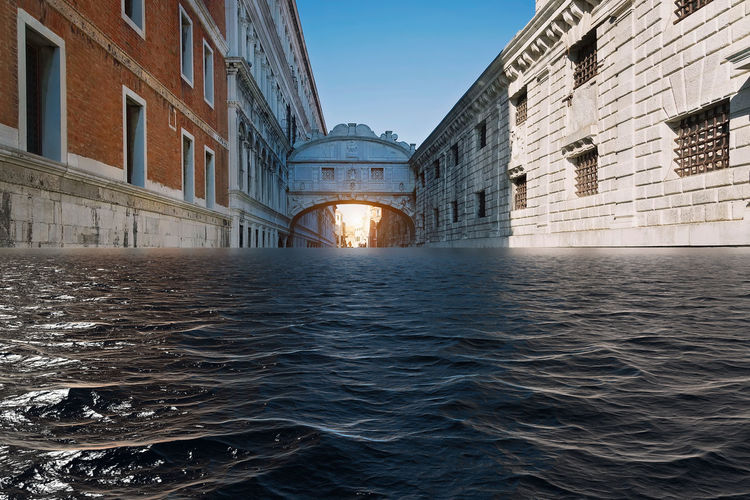 Surface level of canal by buildings against clear sky