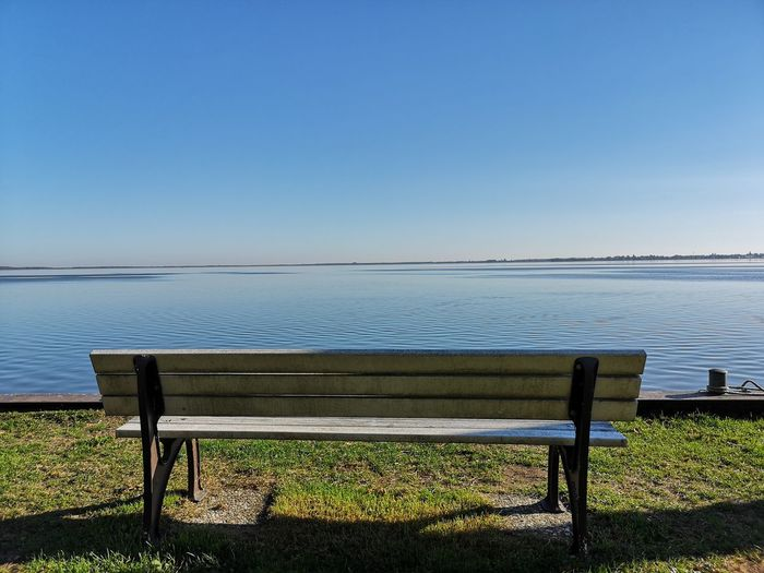 Empty Bench By Sea Against Clear Blue Sky