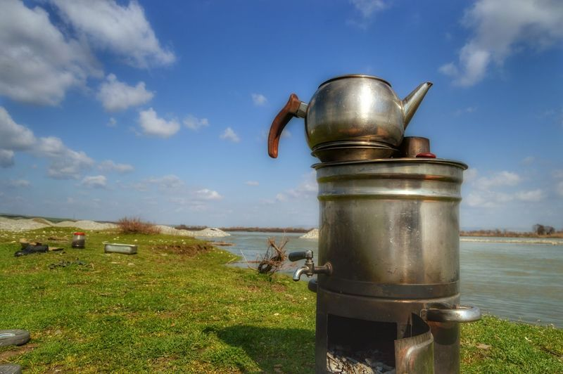 Teapot on metal container at riverbank against sky