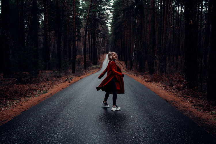 Full length of woman on road in forest