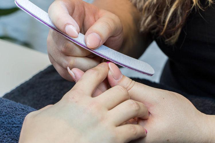 Woman Giving Shape For Customer Fingernail