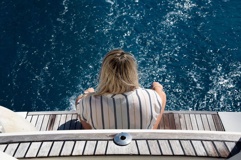 Rear view of woman sitting in water