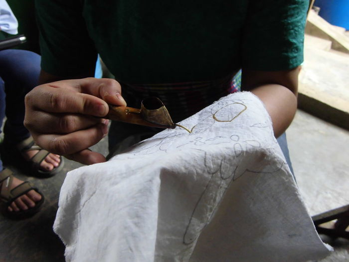 Midsection of woman making design on textile