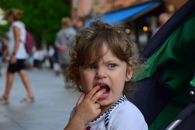 Close-up of cute girl with fingers in mouth looking away