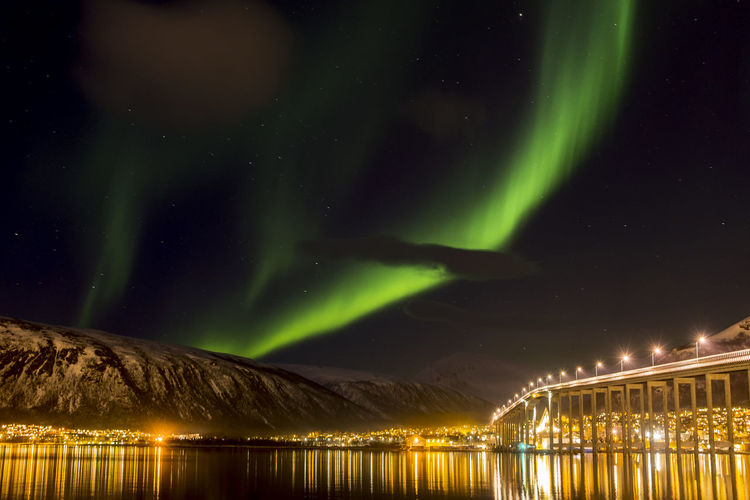 Illuminated bridge over river against aurora borealis