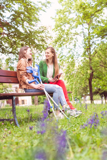 Happy sisters talking while sitting on bench at park