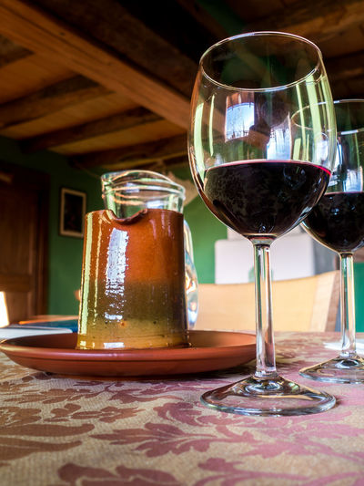 Glass of red wine on a table in rustic restaurant Table Food And Drink Drink Refreshment Glass Indoors  Wineglass Freshness Glass - Material Still Life Food Alcohol Transparent Wine Close-up No People Focus On Foreground Drinking Glass Red Wine Restaurant Crockery